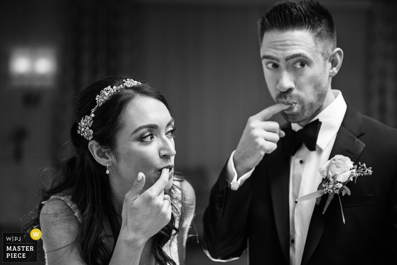 Bride and groom simultaneously lick cake off their fingers while making surprised reactions at Edgewood Country Club NJ wedding - New Jersey, United States Wedding Photography -  | Edgewood Country Club, New Jersey