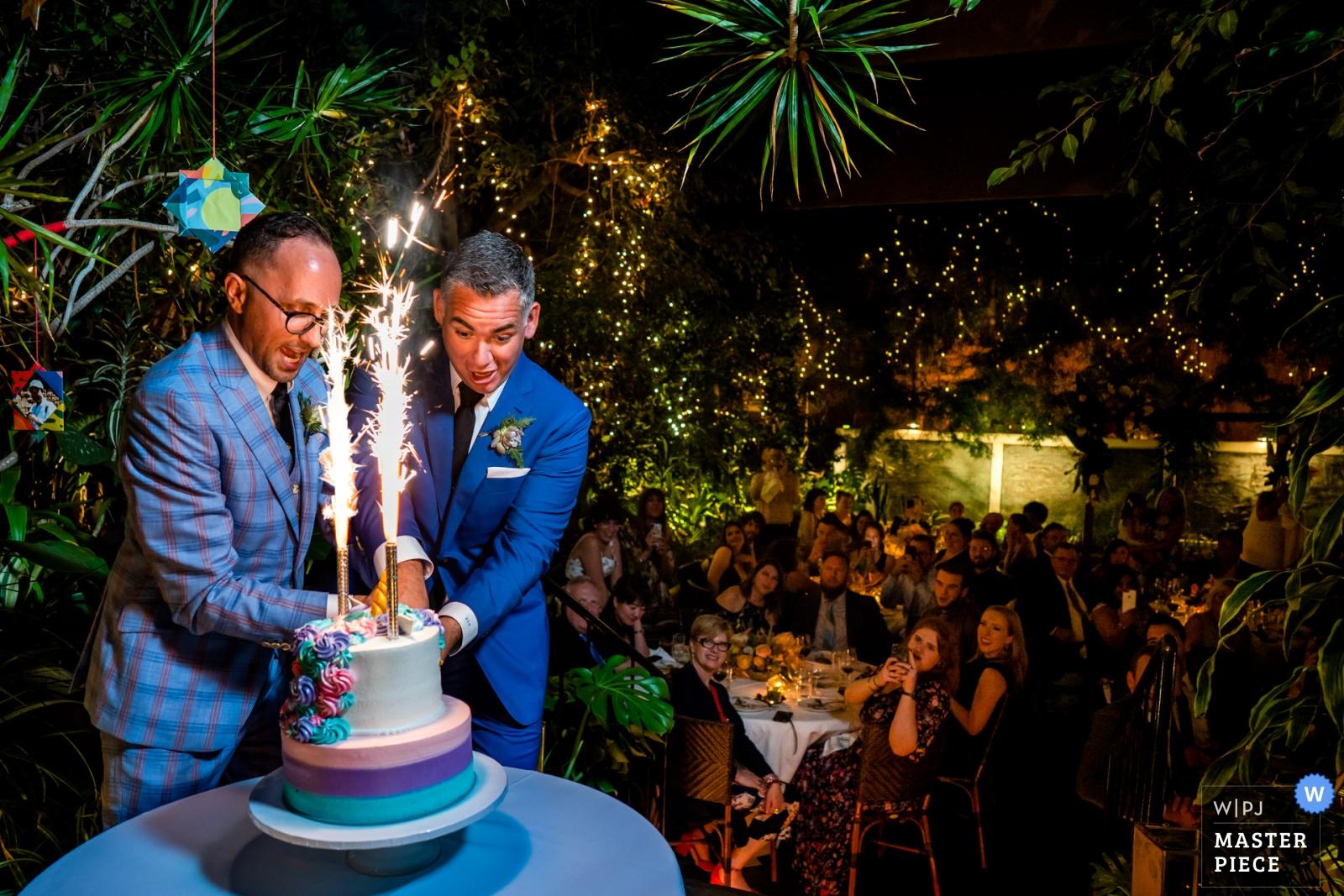 Wedding photo by Bee Two Sweet Photography, two grooms cut into their firecracker topped unicorn wedding cake - Arlington, Virginia Wedding Photography -  | Michael's Restaurant, Santa Monica CA