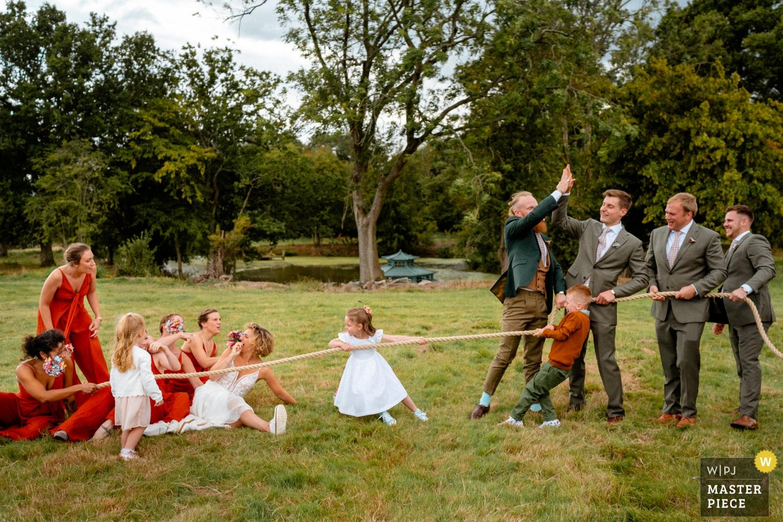 Bride and bridesmaids loose tug of war with groomsmen - Hertfordshire, England Wedding Photography -  | Swallows Oast, Ticehurst, UK