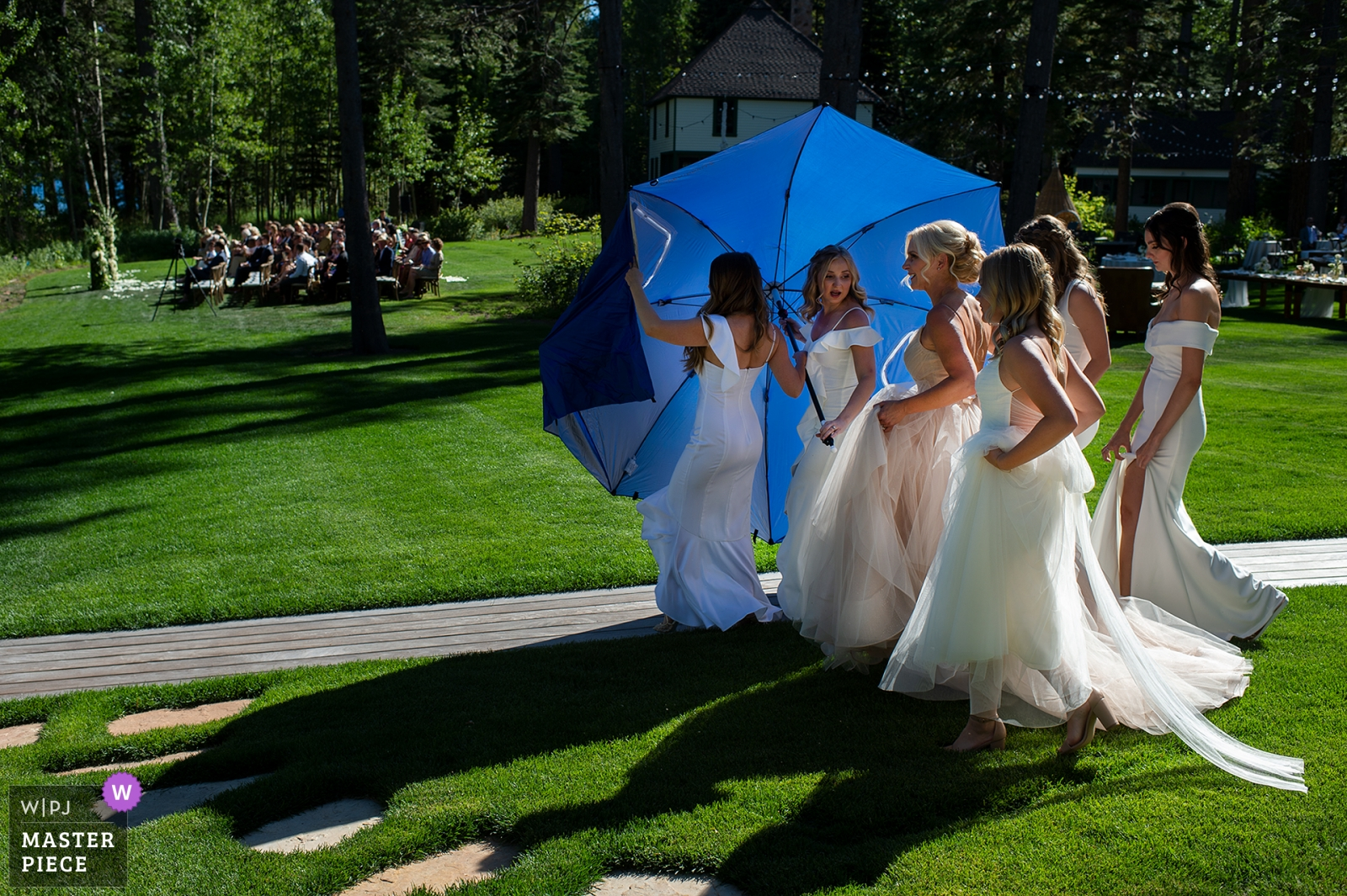 Bridesmaids hide the bride behind an umbrella on the way to her ceremony. - Carson City, Nevada Wedding Photography -  | Private Residence, West Shore Lake Tahoe, CA
