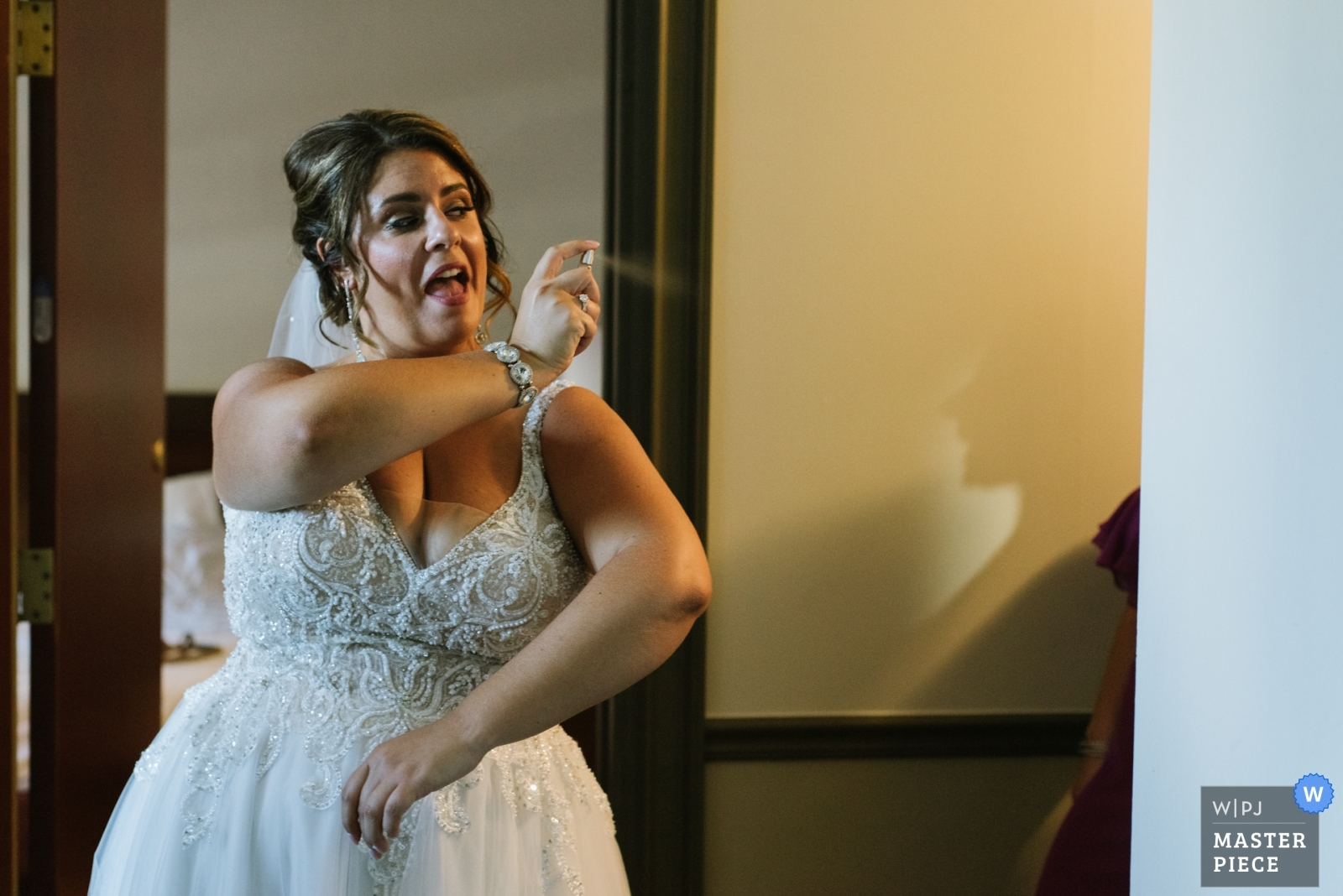A bride spritzes a bridesmaid, who can only be seen by her shadow, with perfume. - Schenectady, New York - Upstate Wedding Photography -  | The Belvedere Inn