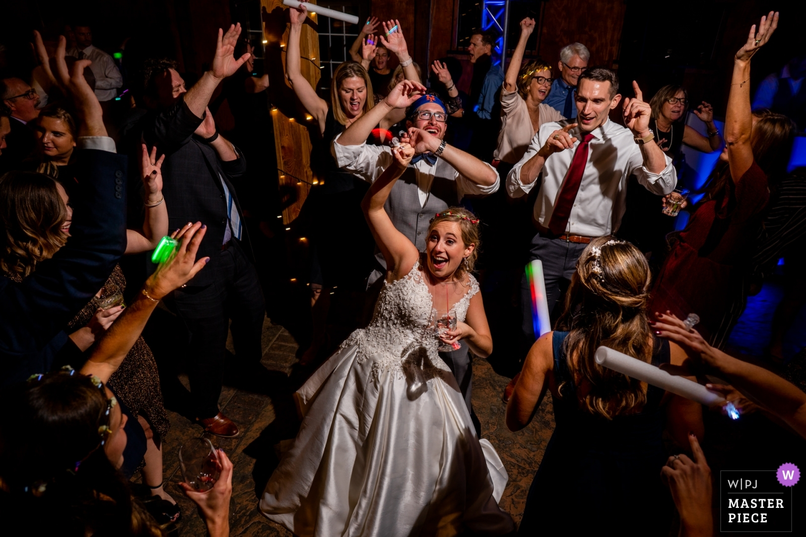 The bride is surrounded by her friends on the dance floor. Wedding photo by Bee Two Sweet Photography. - Arlington, Virginia Wedding Photography -  | Bluemont Vineyard