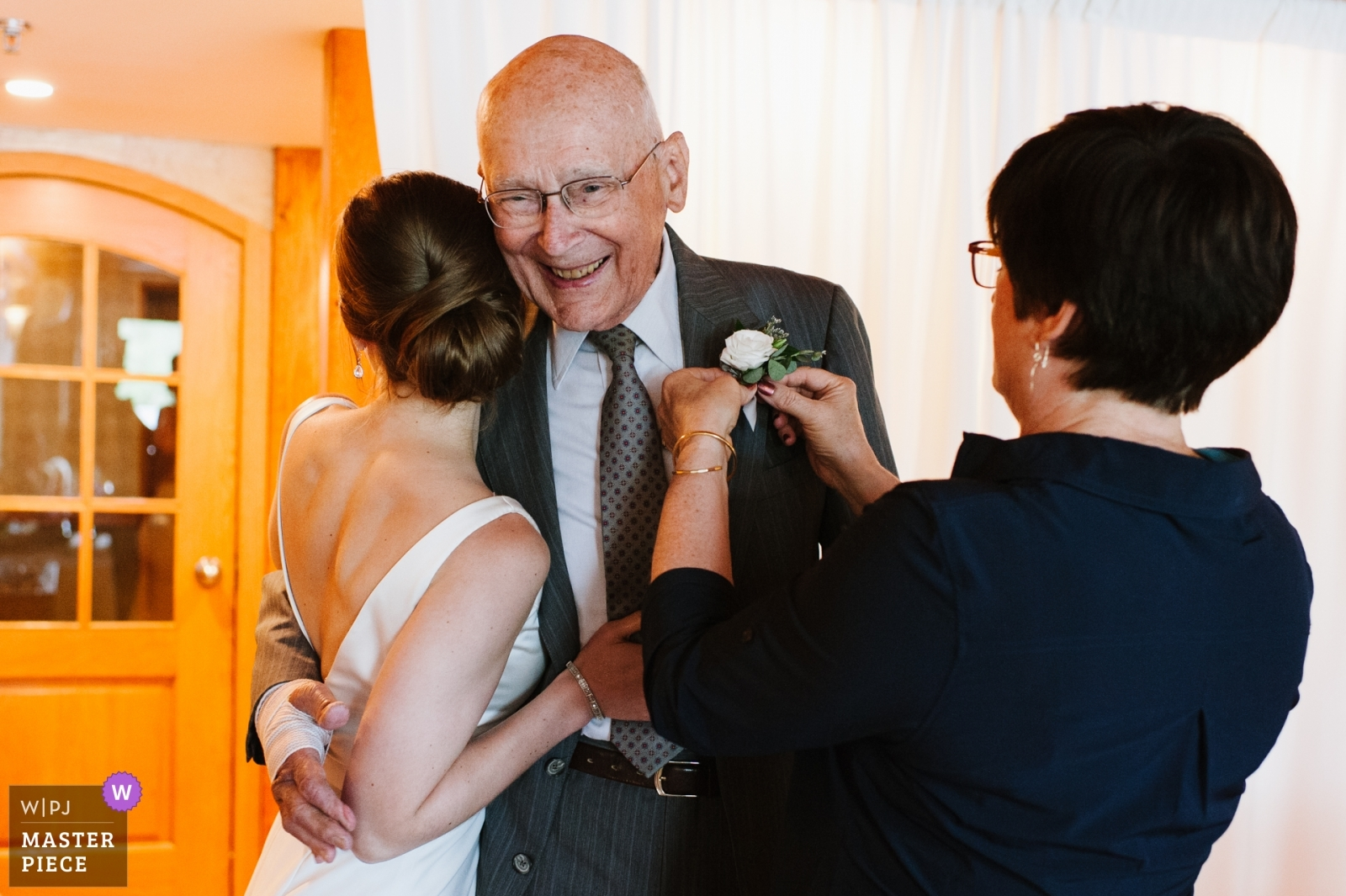 A bride's grandfather smiles as he is hugged by the bride and his daughter pins on his boutonniere. - Schenectady, New York - Upstate Wedding Photography -  | Golden Arrow Lakeside Resort