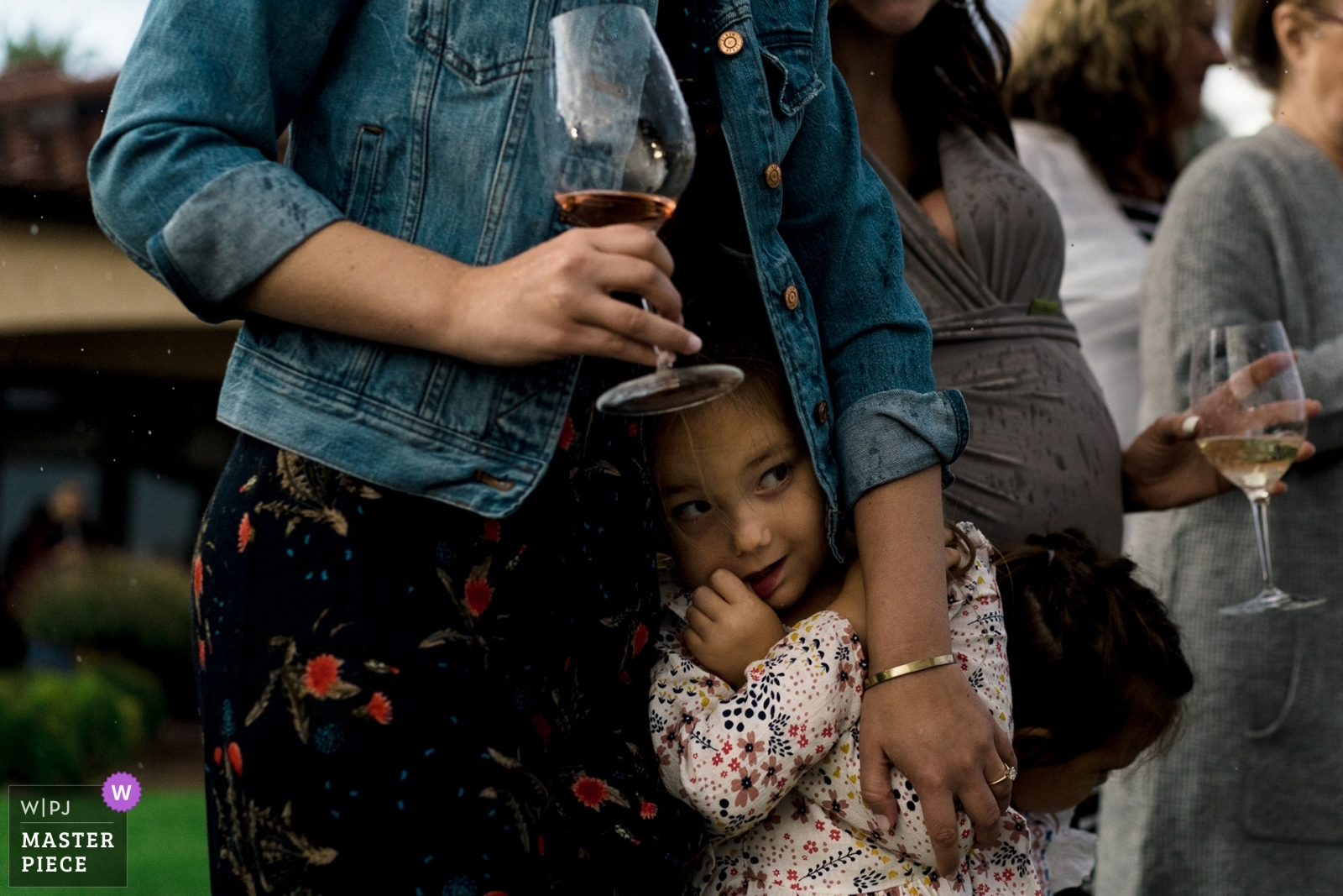 child hides from rain in moms coat during outdoor wedding ceremony - Seattle, Washington Wedding Photography -  | benson Winery