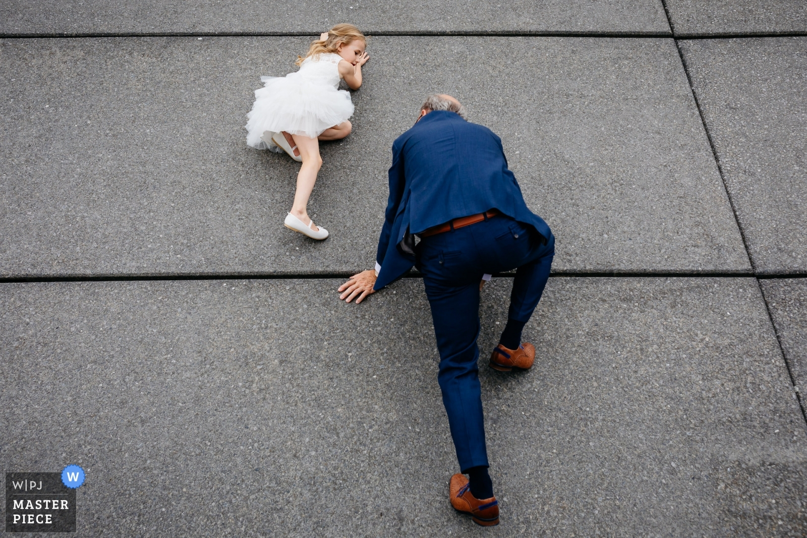 daughter of the bride and groom and her granddad are climbing a wall. - Utrecht, Netherlands Wedding Photography -  | Outside the venue, Hotel New York, Rotterdam, Netherlands