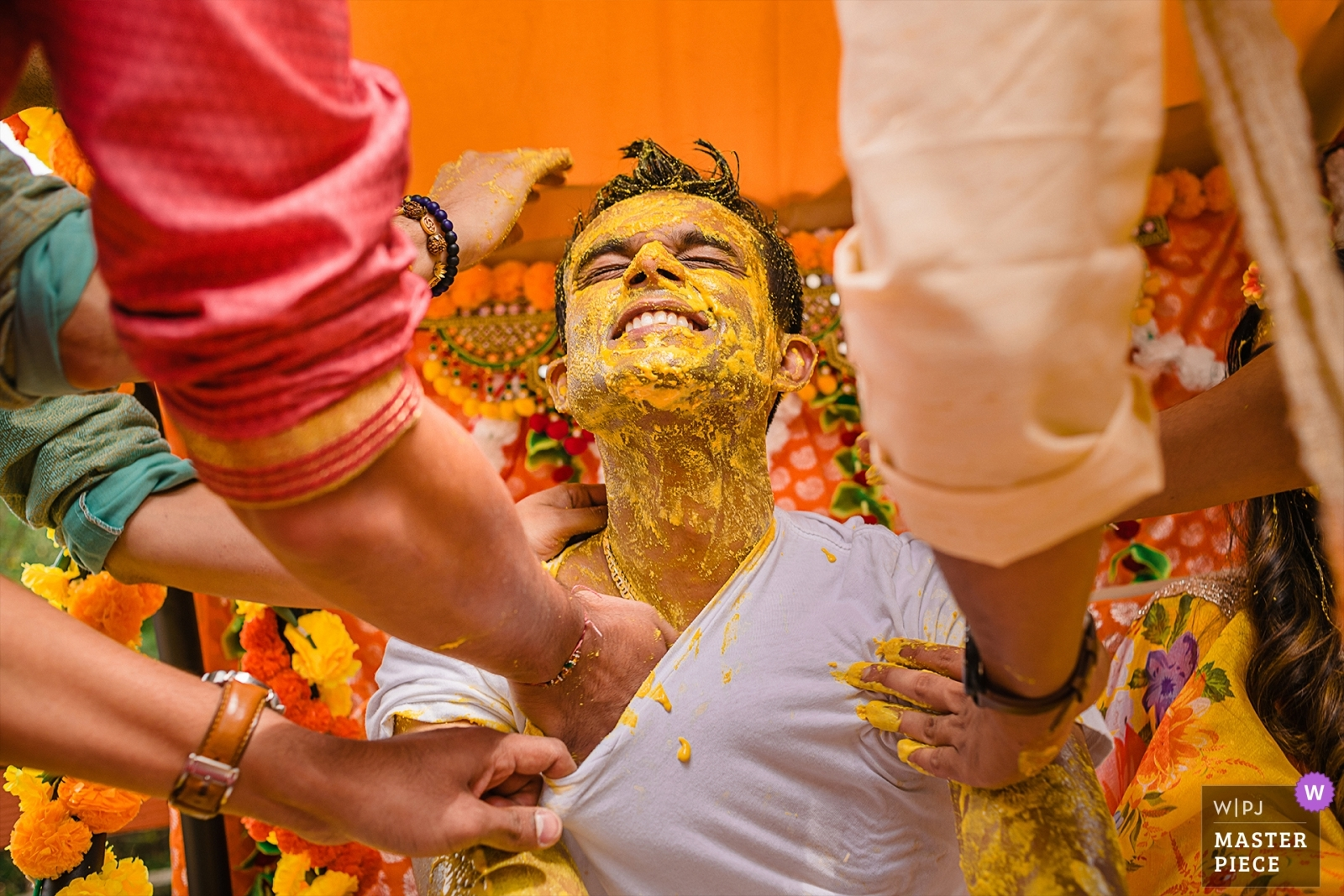 Haldi being put on the groom before his wedding - Maryland, United States Wedding Photography -  | Pre-Wedding Ceremony at brides home