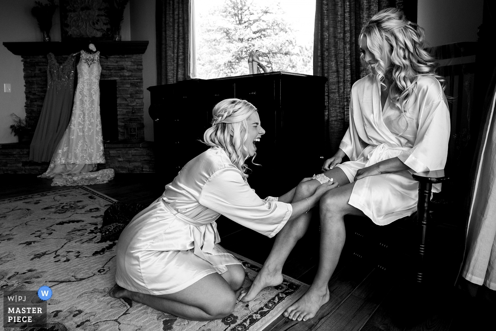 The maid of honor laughs while placing the garter on the bride while getting ready for the wedding. - Denver, Colorado Wedding Photography -  | The Broadmoor