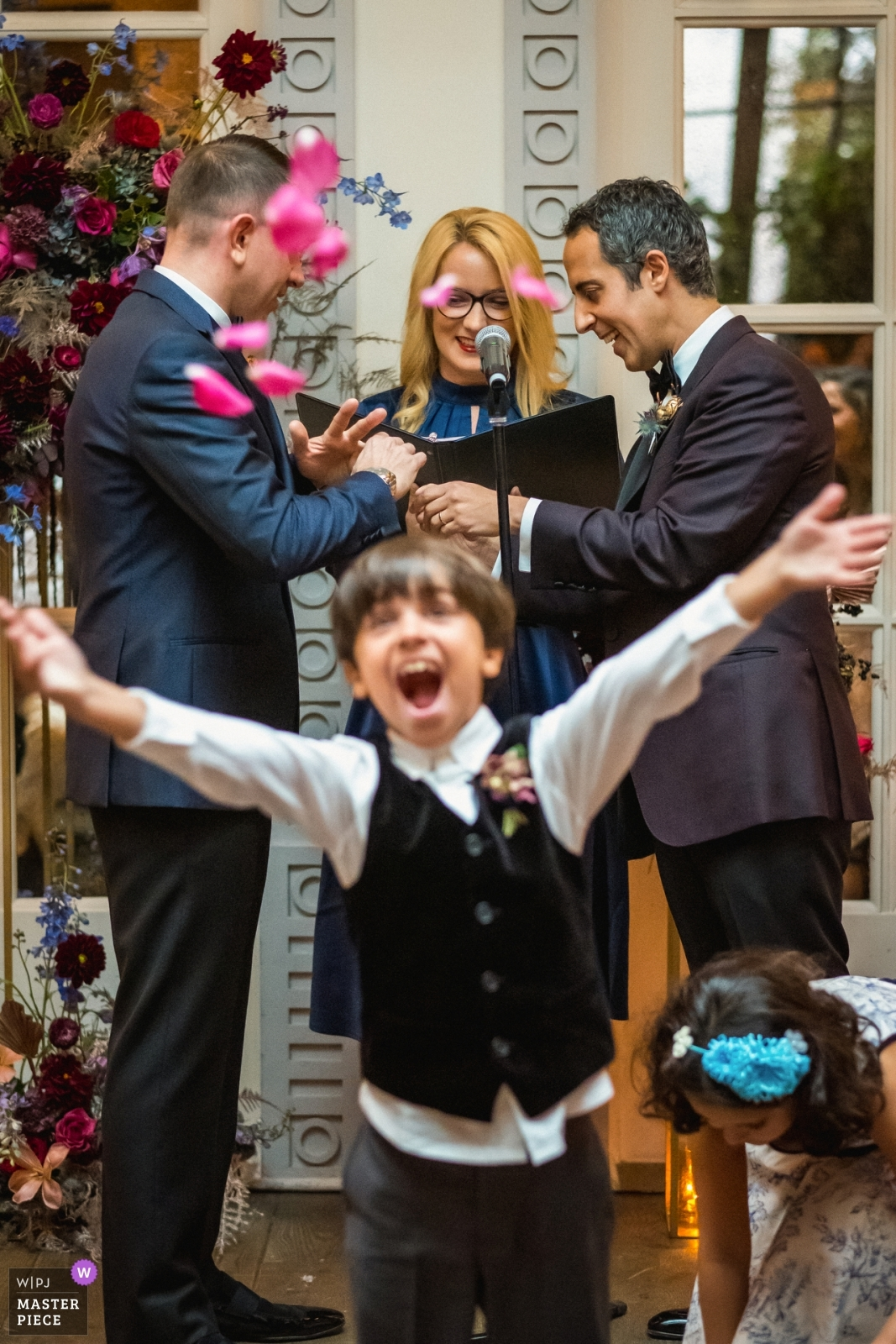 The ring-bear and the son of couple abruptly throws rose petals to celebrate while they exchange rings during their wedding ceremony. - Los Angeles, California - Southern Wedding Photography -  | Spago, Beverly Hills, California