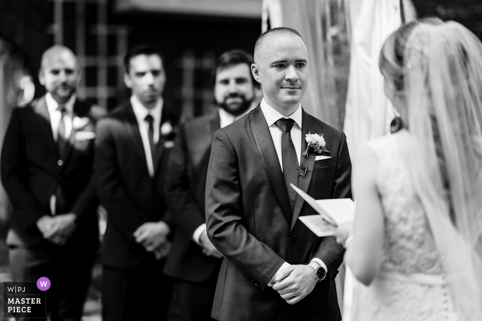 Groom shedding a tear while the bride reads her vows and the Groomsmen look on. - New Jersey, United States Wedding Photography -  | Ceremony Location