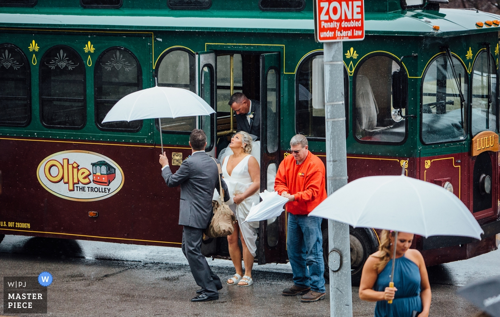 Bride getting off of trolley looking up at it raining - Omaha, Nebraska Wedding Photography -  | Ceremony location