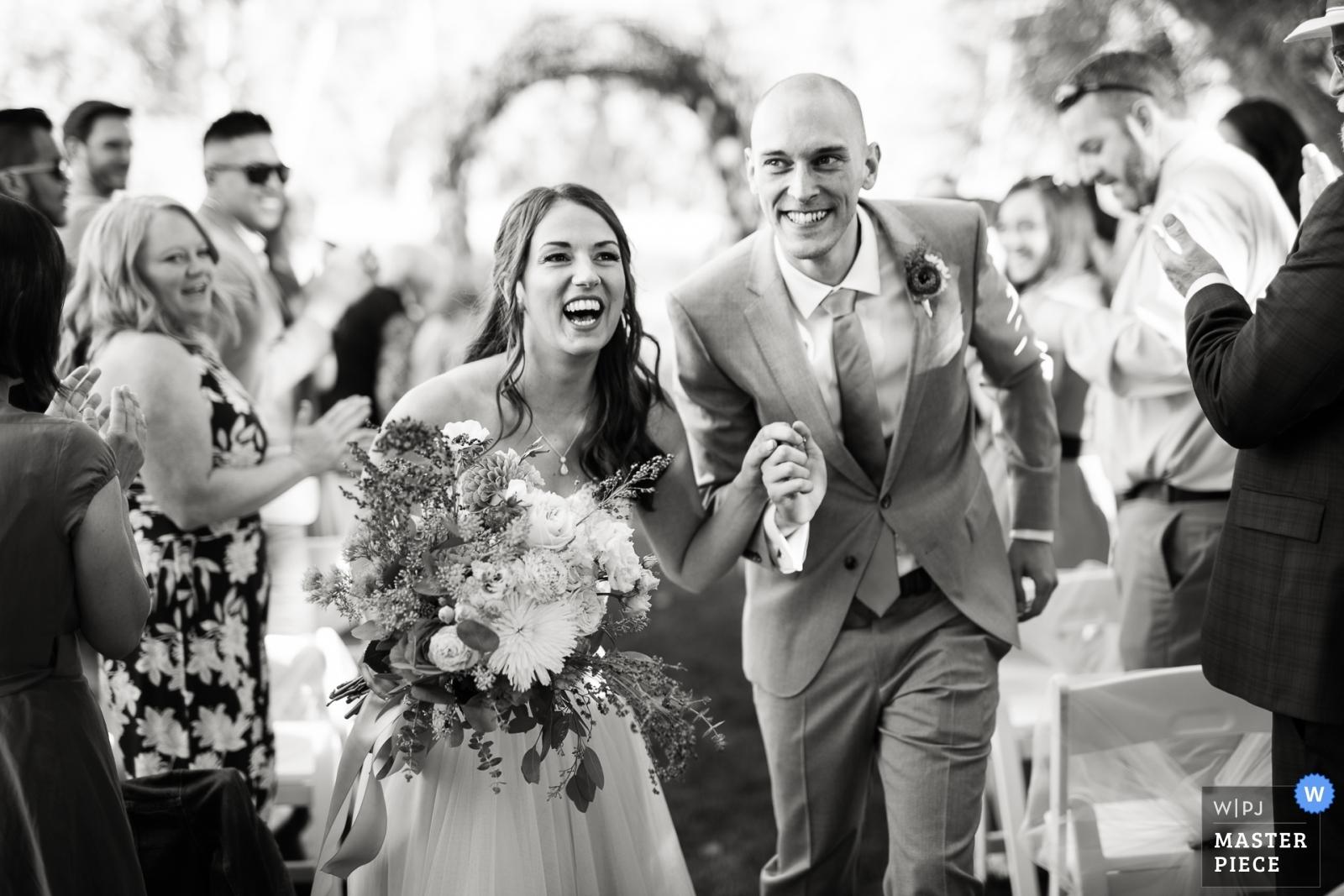 Bride and groom's departure from the ceremony. - Denver, Colorado Wedding Photography -    Backyard wedding, Longmont, Colorado