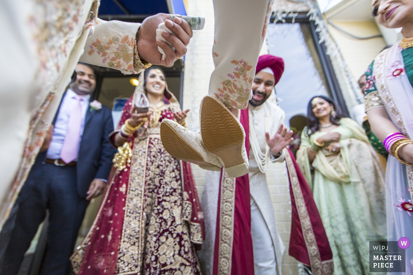 Jus retrieves his shoes, as the tender exchanges hands, following a brisk negotiation after the ceremony. - Virginia, United States Wedding Photography -  | Sikh Association of Baltimore, Randallstown, MD