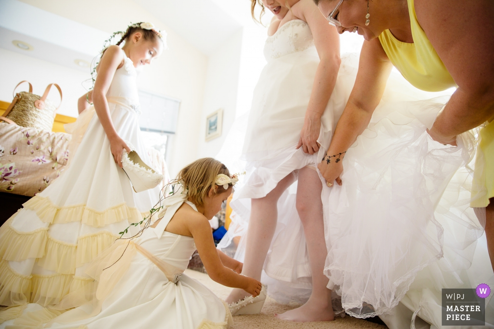 The bride gets help with her shoes from her flower girls and maid of honor. - Lake Tahoe, California - Northern Wedding Photography -    South Lake Tahoe, Private Home