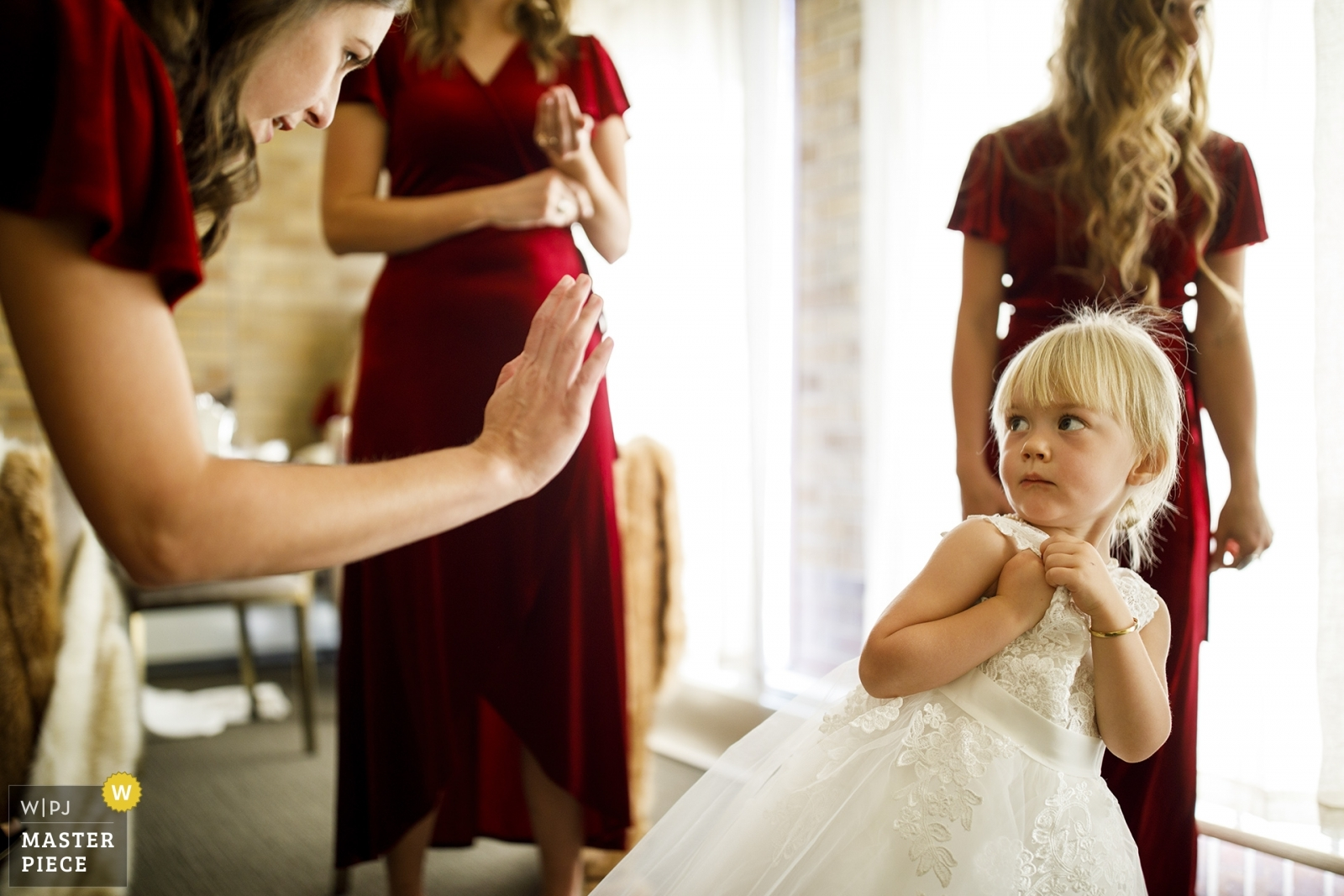 The flower girl reacts when a bridesmaid prompts her for a high-five while getting ready for the wedding. - Denver, Colorado Wedding Photography -  | Our Lady of Lourdes Catholic Church, Denver, CO