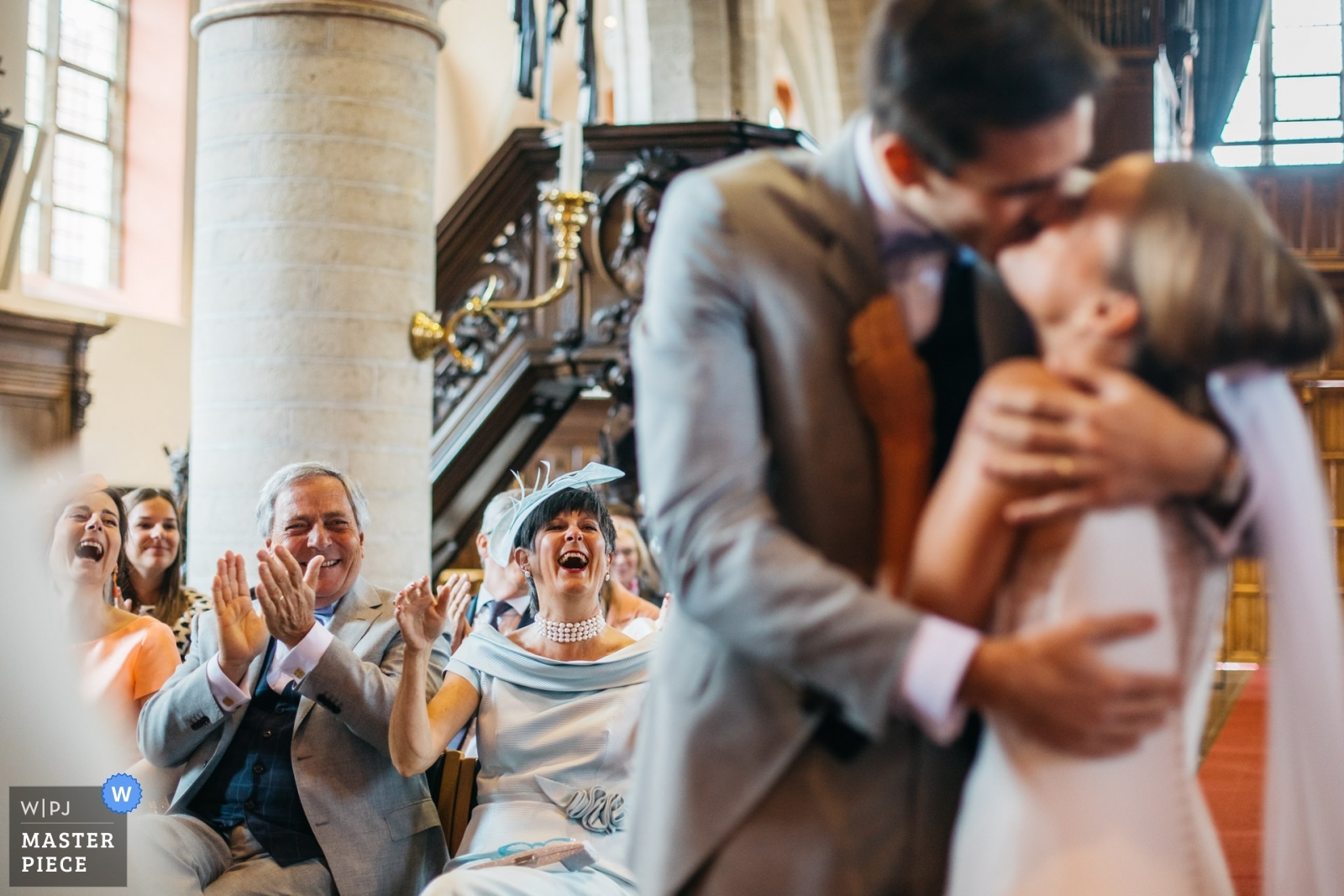 "the couple kisses right after the priest declared ""the couple may kiss as ling as people applaud"" - Antwerpen, Flanders Wedding Photography -  