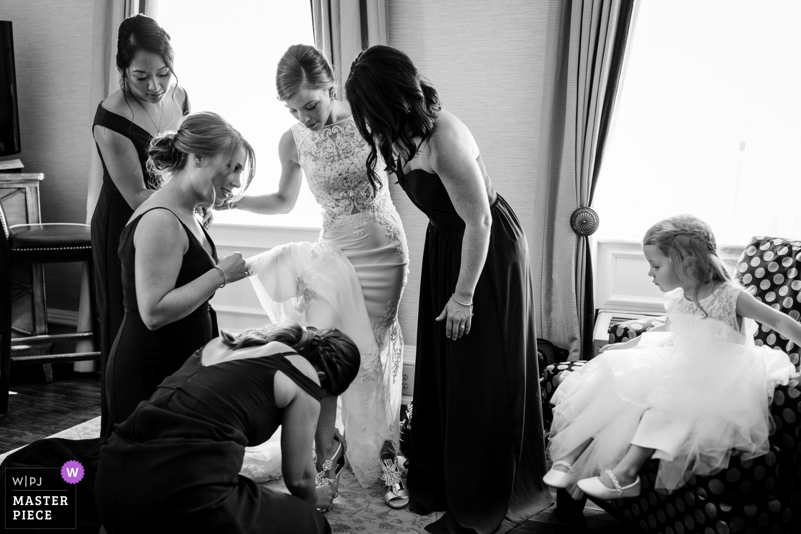 Bridesmaids help bride put her shoes on as the flower girl watches - New Jersey, United States Wedding Photography -  | Hotel