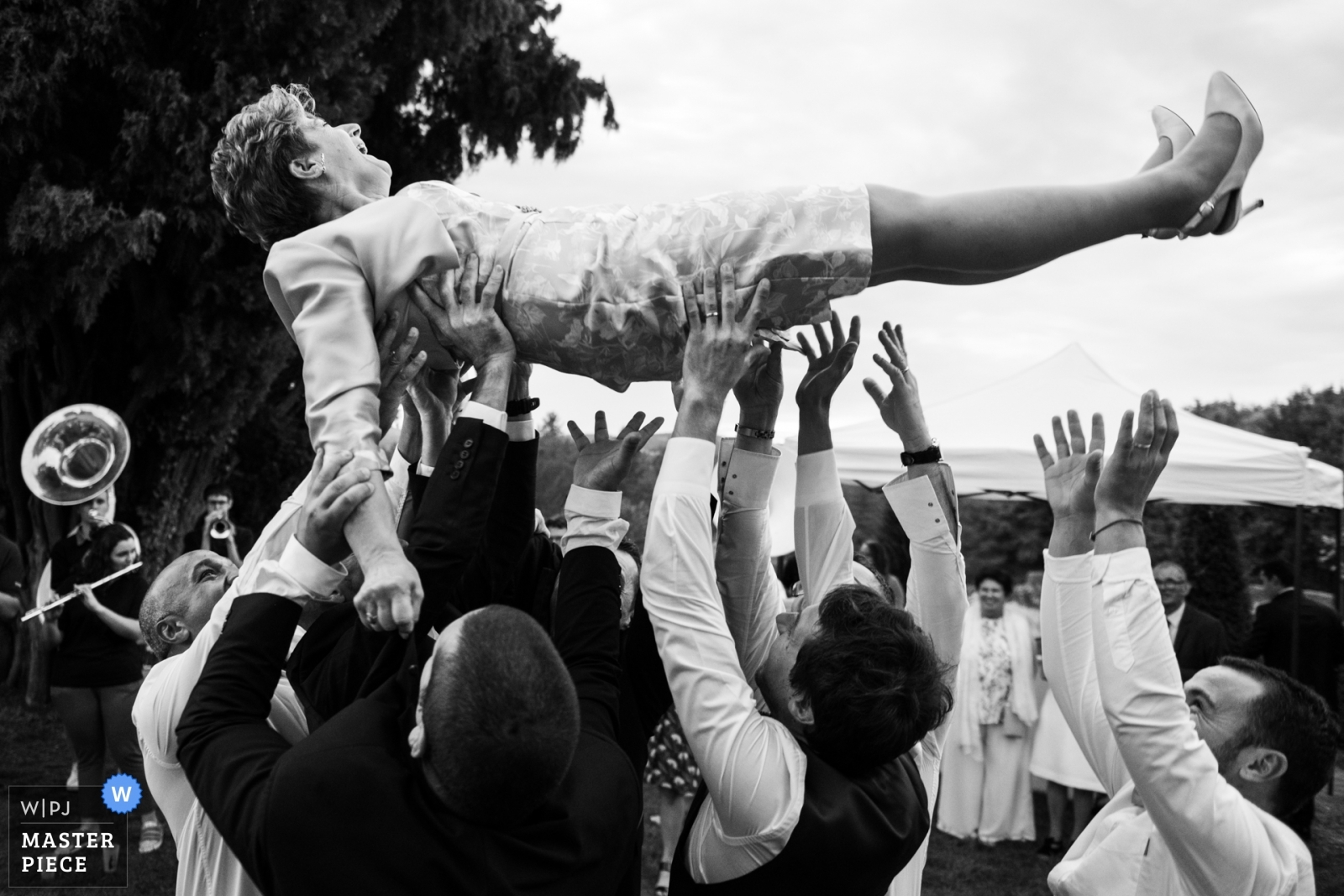 Boys are throwing the mother in law in the air - Nouvelle-Aquitaine, France Wedding Photography -  | Jardins d'Eyrignac