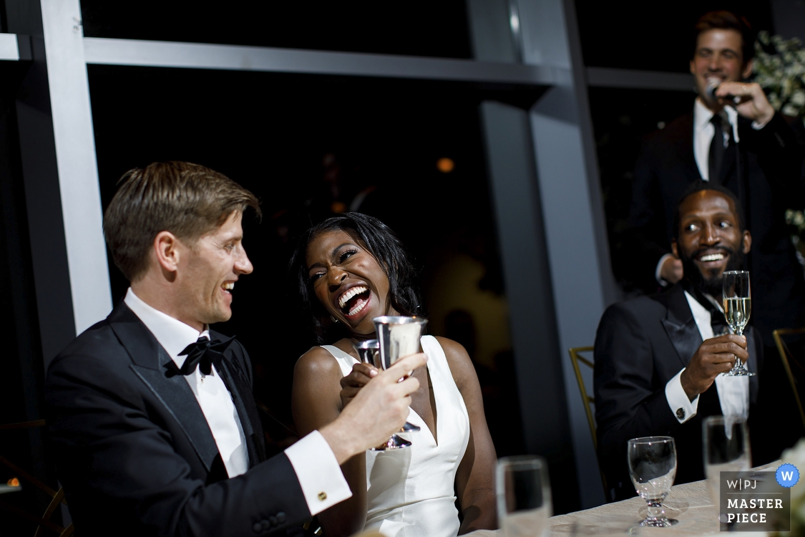 The bride and groom share a laugh during a toast at the Denver Museum of Nature and Science - Denver, Colorado Wedding Photography -  | Denver Museum of Nature and Science