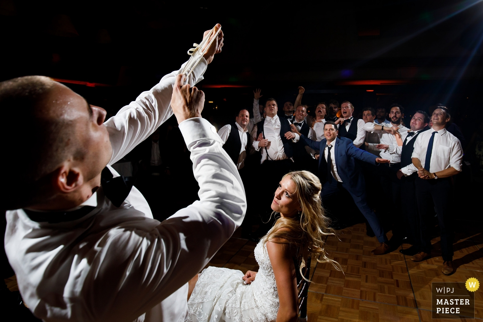 The groom prepares to shoot the garter as single guys jostle for position on the dance floor during a wedding reception at The Broadmoor. - Denver, Colorado Wedding Photography -  | The Broadmoor Hotel, Colorado Springs, Colorado