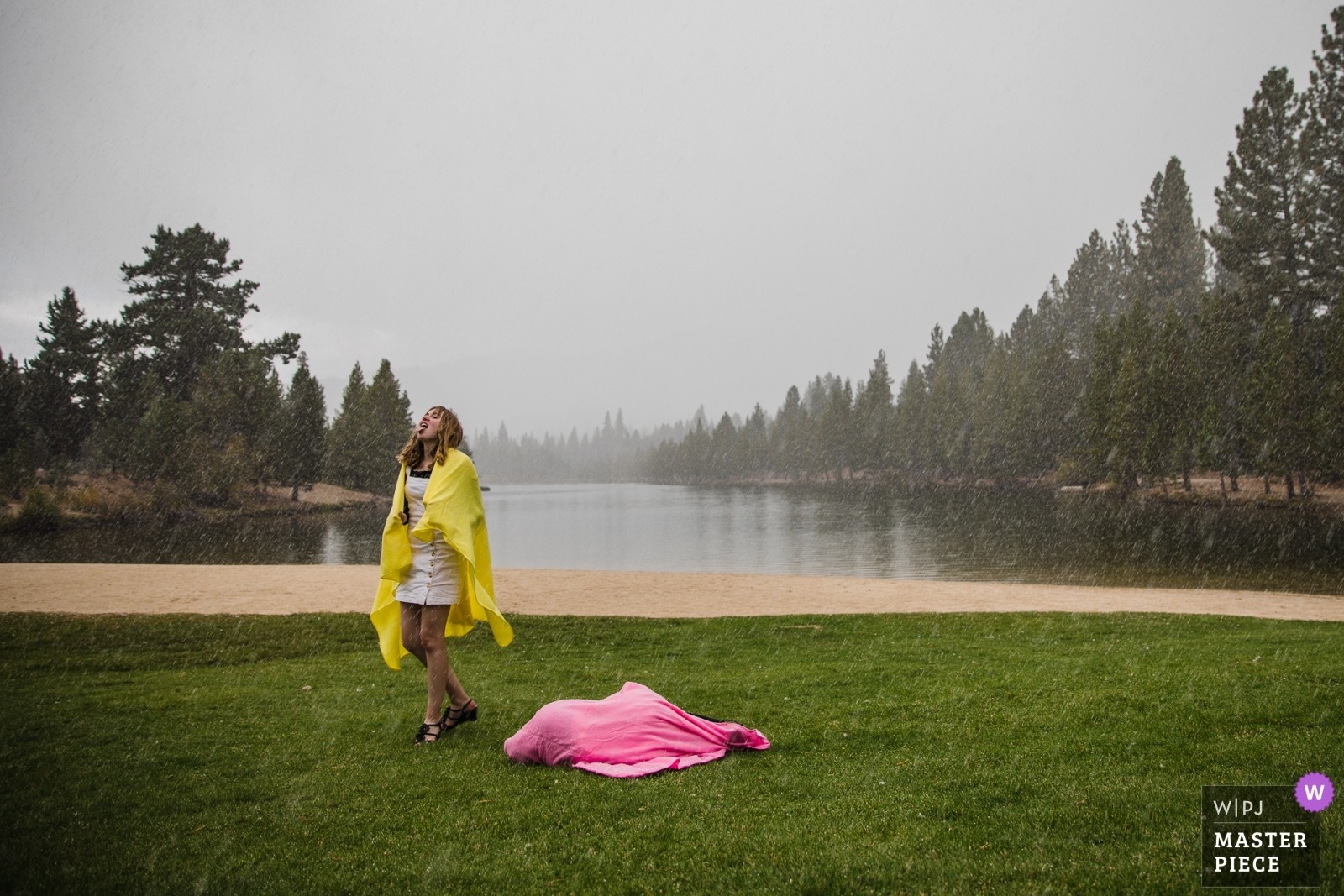 Young wedding guests play in an unexpected September snowstorm, shielded by colorful blankets. - Lake Tahoe, California - Northern Wedding Photography -    Tahoe Paradise Park: South Lake Tahoe, CA