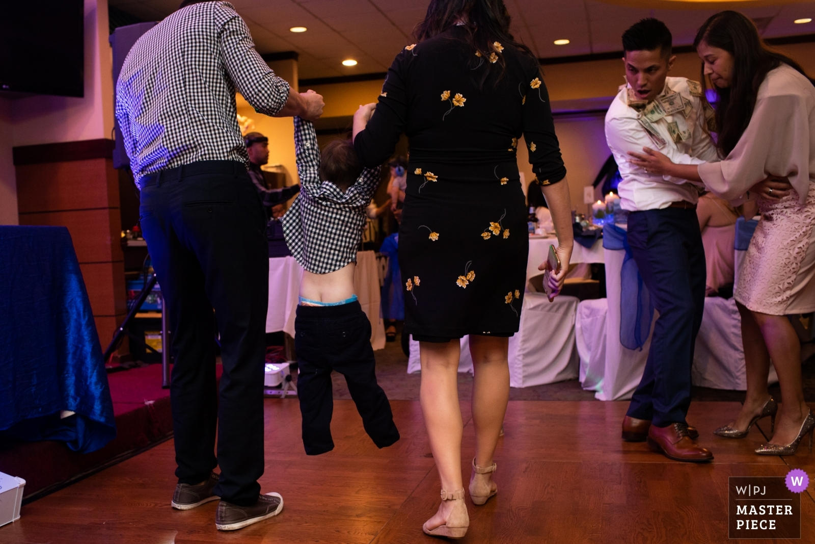 The child is pulled out of the dance floor by the parents - San Jose, California - Northern Wedding Photography -  | New Port Restaurant in Cupertino