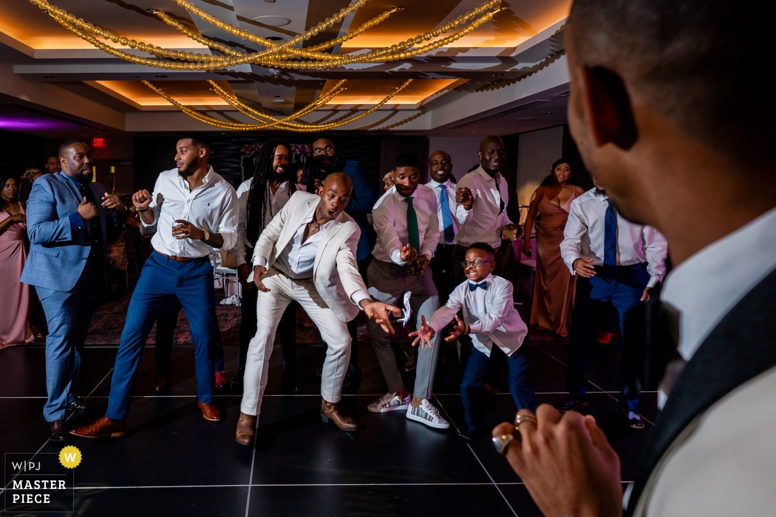 Wedding photo by Bee Two Sweet Photography, a kid and a groomsman dive for the garter - Arlington, Virginia Wedding Photography -  | University of Maryland Hotel, College Park, MD, USA