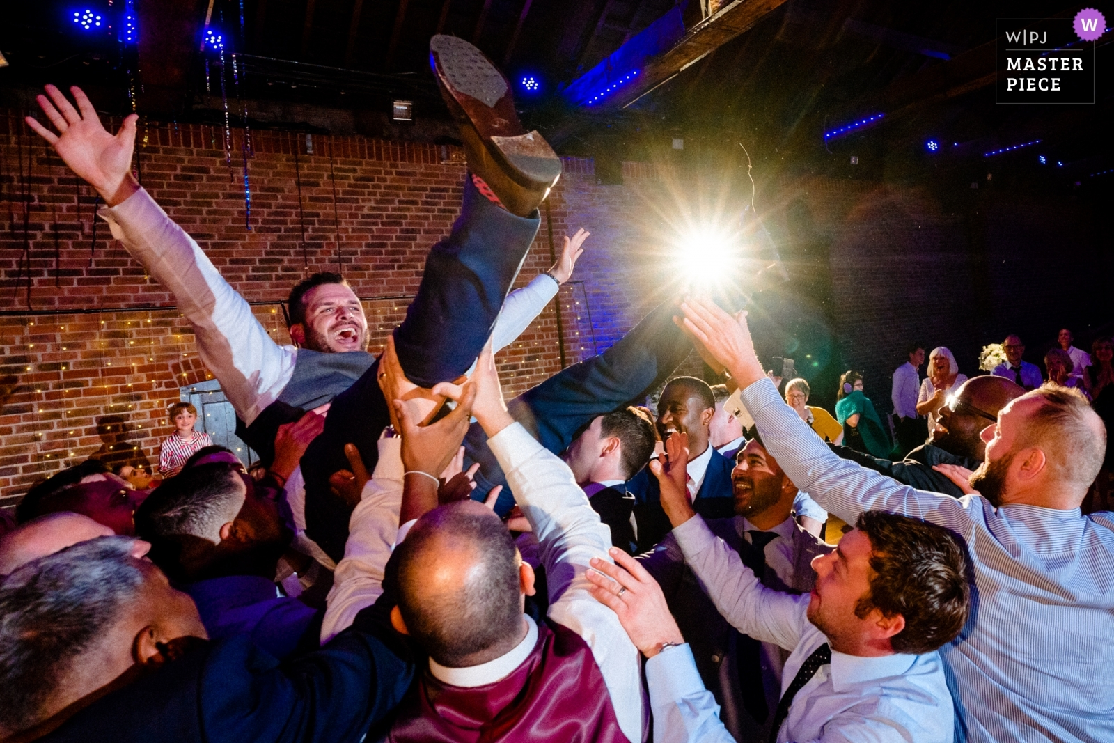 Groom during Greek dancing at the reception. - Hertfordshire, England Wedding Photography -  | The Brewery, London, UK