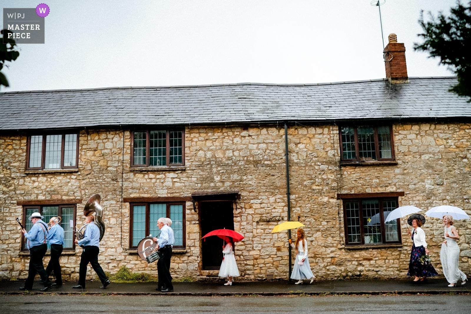 Kate walking to church, led by a band. - Hertfordshire, England Wedding Photography -  | Brackley, Northamptonshire, UK