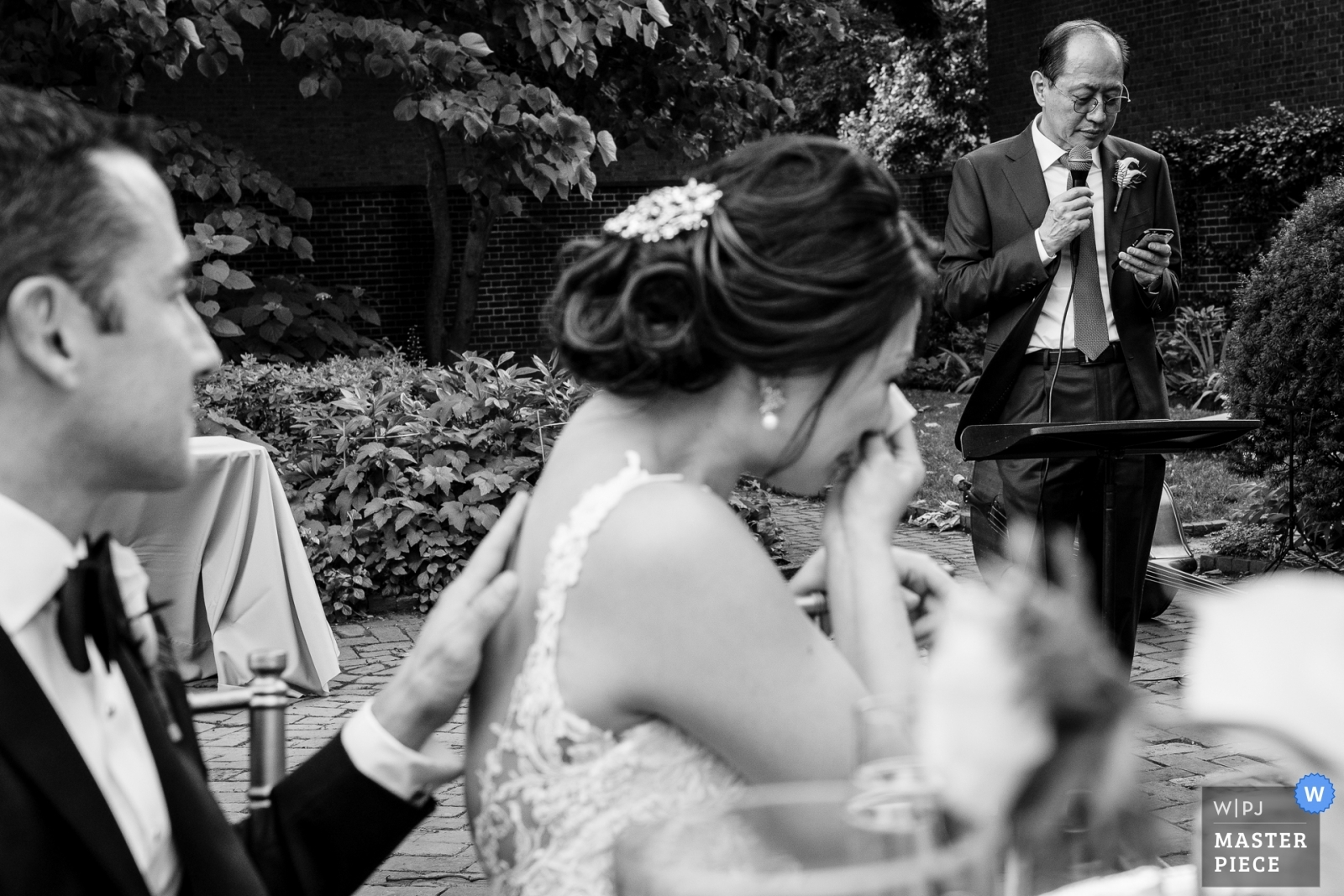 Bride crying as the Groom comforts her during her father's welcome toast - New Jersey, United States Wedding Photography -  | Reception Venue