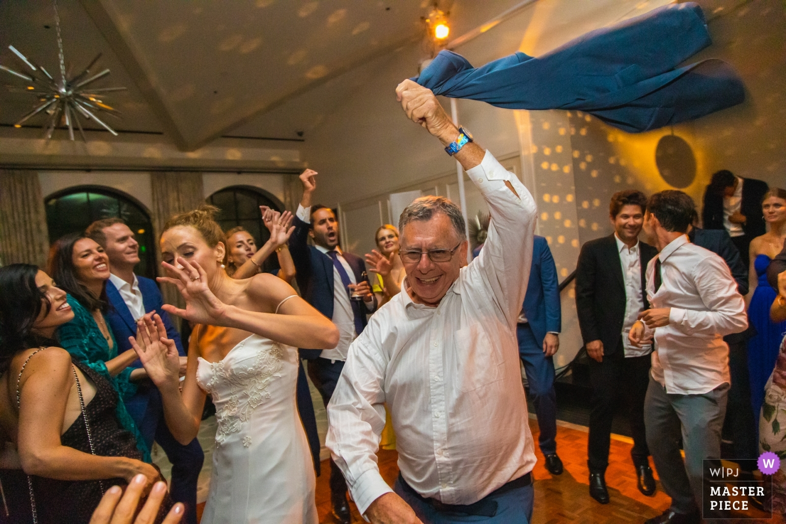 The bride dodges her step-father's jacket being swung in the air on the dance floor. - Los Angeles, California - Southern Wedding Photography -  | Hotel Bel-Air, Los Angeles, California