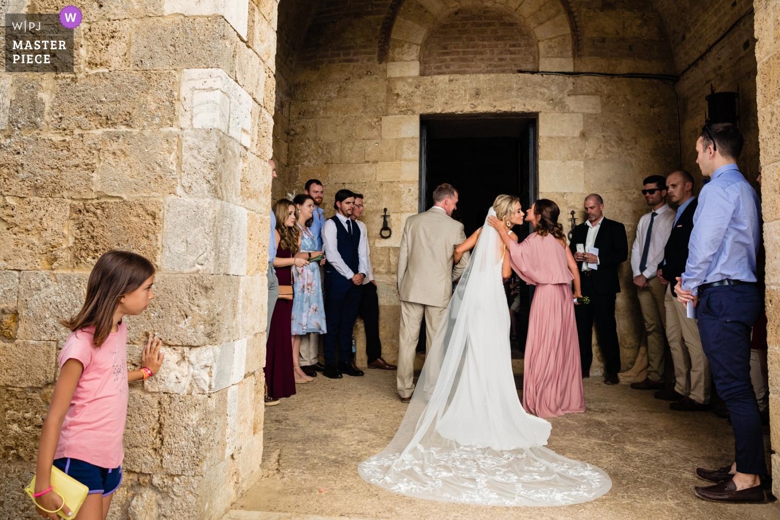 Tourist child peeps at bride outside church preparing to walk in, bridesmaid air kiss. - Dublin, Leinster Wedding Photography -  | San Galgano, Tuscany, Italy