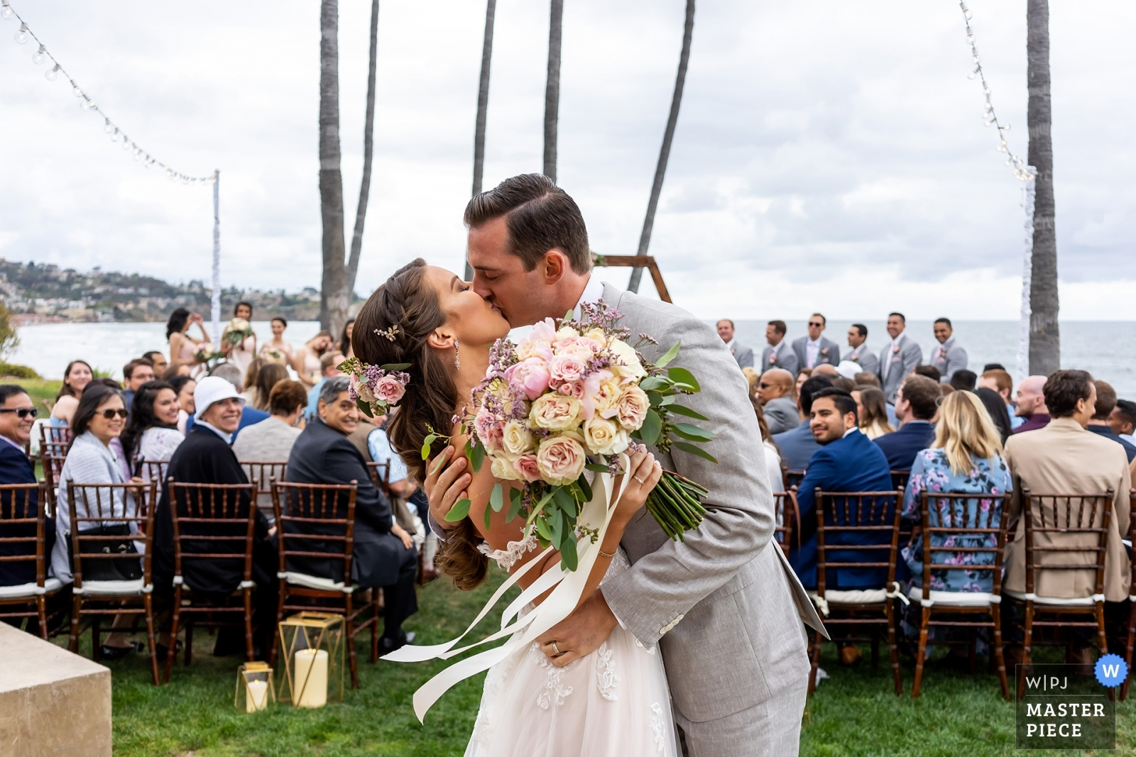 The bride and groom kiss after their wedding ceremony. - San Diego, California - Southern Wedding Photography -  | Scripps Seaside Forum, La Jolla, California.
