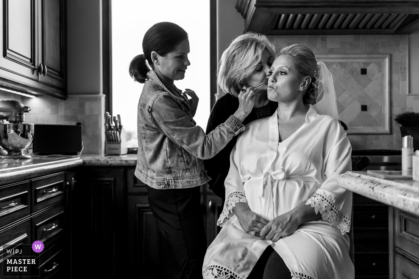 Mom sneaks in a kiss while her daughter is having her makeup put on. - San Diego, California - Southern Wedding Photography -  | The brides mothers house. Rancho Santa Fe, California.