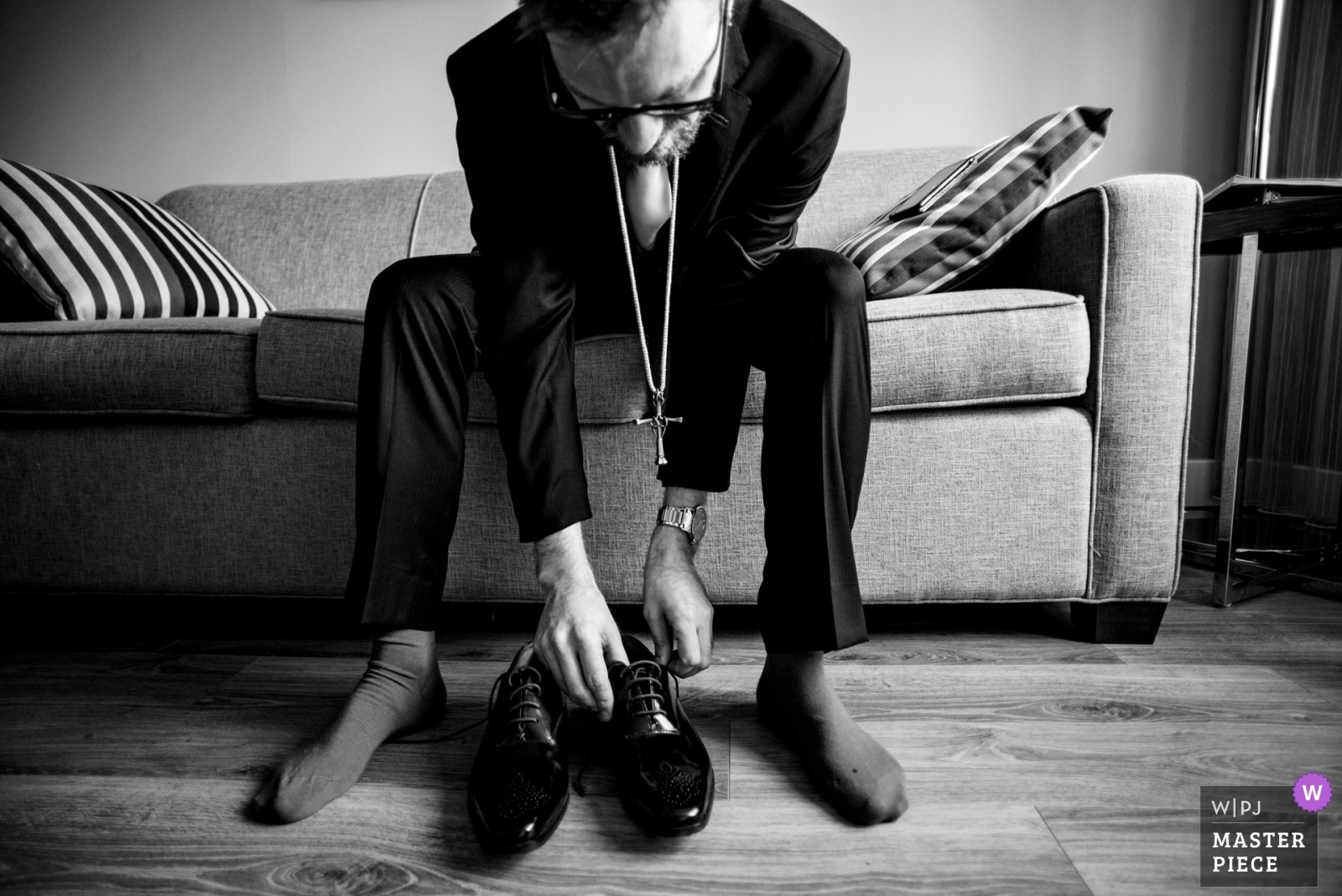 Groom putting on his shoes, wearing his deceased father's cross in his honour - Montreal, Quebec Wedding Photography -  | Montreal, Quebec, Canada