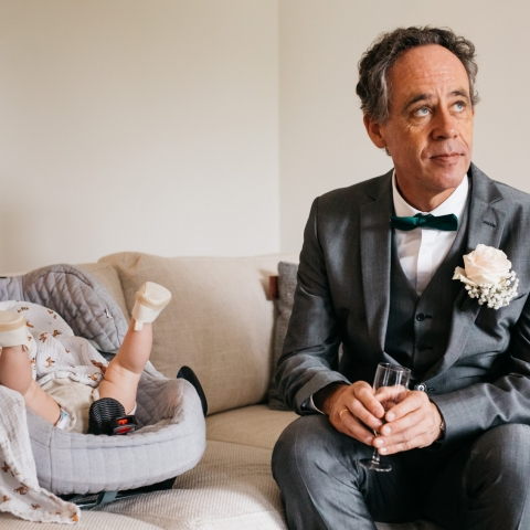 baby is not up for sleeping yet while her granddad is sitting next to her - Antwerpen, Flanders Wedding Photography -  | bride and groom's house