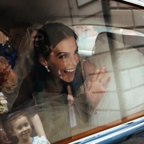 Bride waves at the flowergirl as she arrives for the ceremony - London, England Wedding Photography -  | St Bride's Church, London